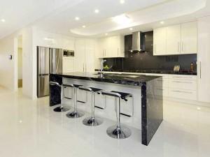 Белая кухня с черной барной стойкой.