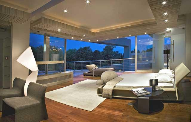 Интерьер современной спальни с выходом на терассу и панорамным видом.